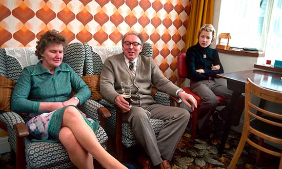 family-sitting-in-a-1970s-lounge-decorated-in-patterned-wallpaper-and-carpet