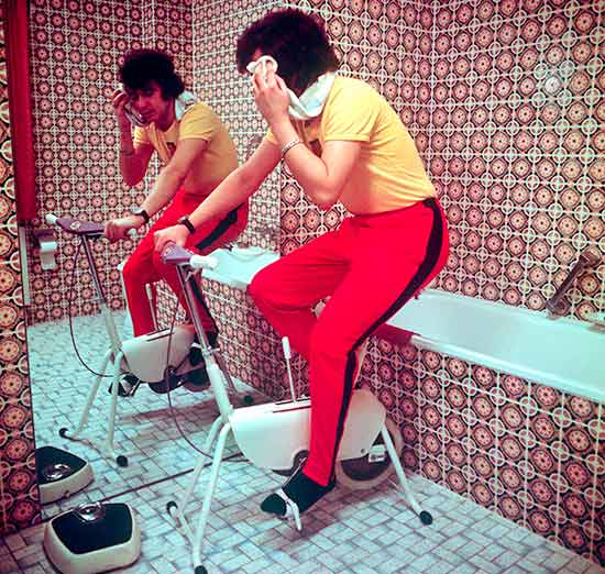 man-on-exercise-bike-in-a-maroon-patterned-bathroom
