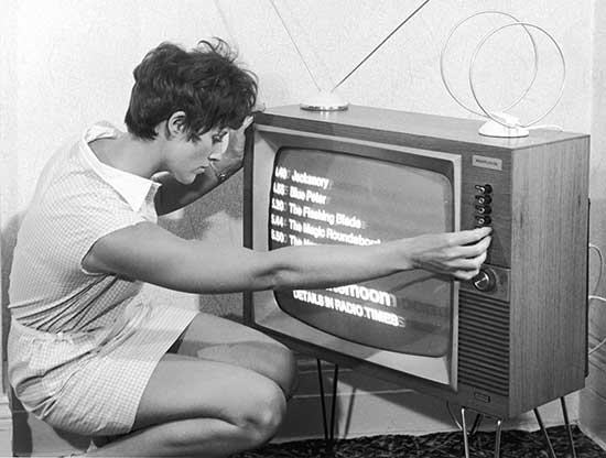 woman-in-sixties-shift-dress-changing-channel-on-a-tv-set