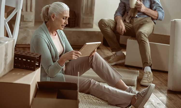 mature lady sitting on the floor looking at a picture frame
