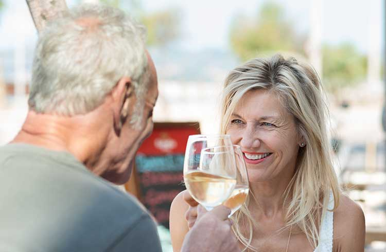 Mature couple drinking white wine, sat outside a restaurant on a sunny day