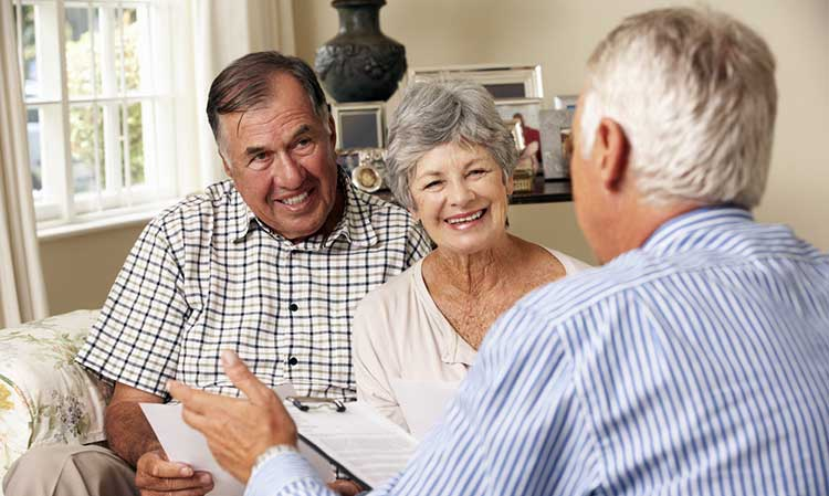 man and wife speaking with an independent expert adviser in their home