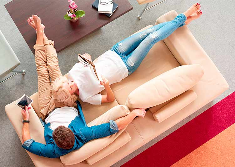 Mature couple relaxing on sofa at home, shot from above