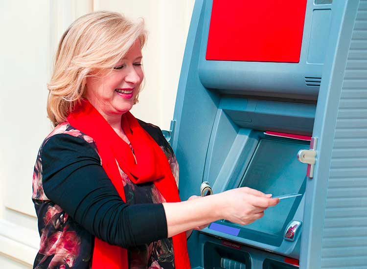 Mature woman withdrawing money from ATM