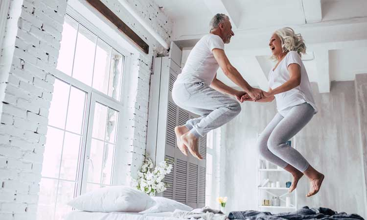 a couple jumping together on the bed