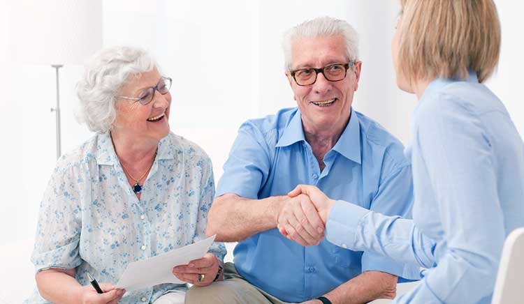 mature couple shaking hands with an independent expert adviser