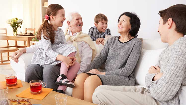 grandparents with their grandchildren sitting on a sofa laughing together