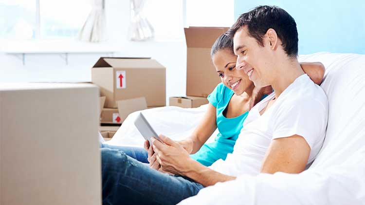 young couple sitting on a sofa surrounded by packing boxes