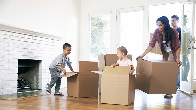 young family bringing boxes into a property
