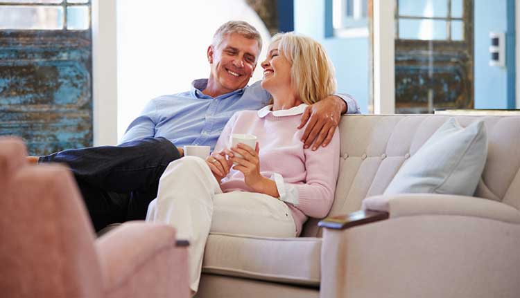 mature couple smiling and sitting on the sofa