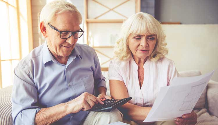 a mature couple looking at floor plans and calculating costs