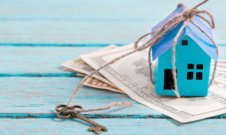 small blue wooden house sitting on bank notes next to a key