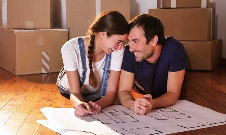 a young couple on the floor looking at floor plans