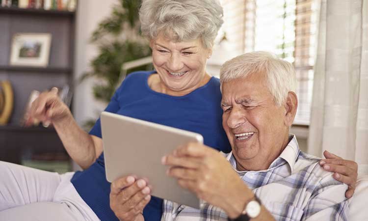 a mature couple laughing whilst looking at a tablet