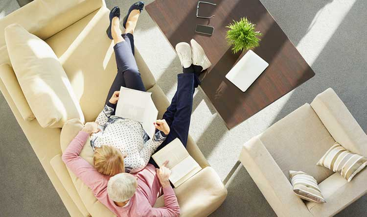 ariel view of a mature couple reading together on the sofa