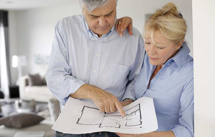 married couple looking at floor plans