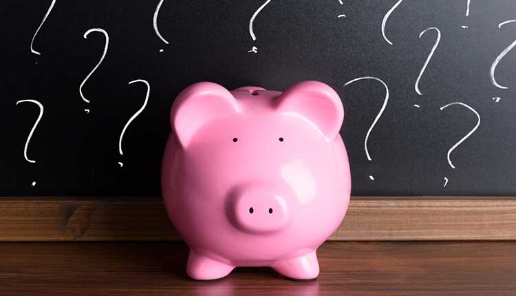 piggy bank and a blackboard with question marks on