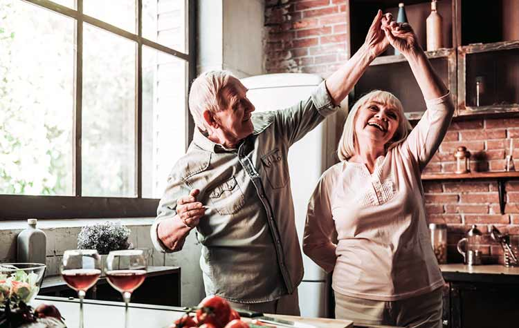 mature couple happily dancing in the kitchen