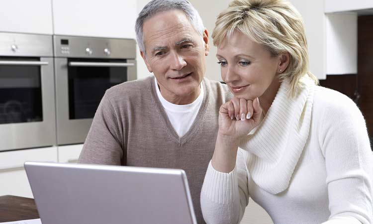 older married couple looking at information on a laptop