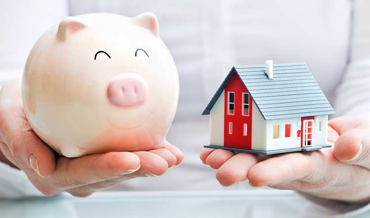 person holding a piggy bank and small house