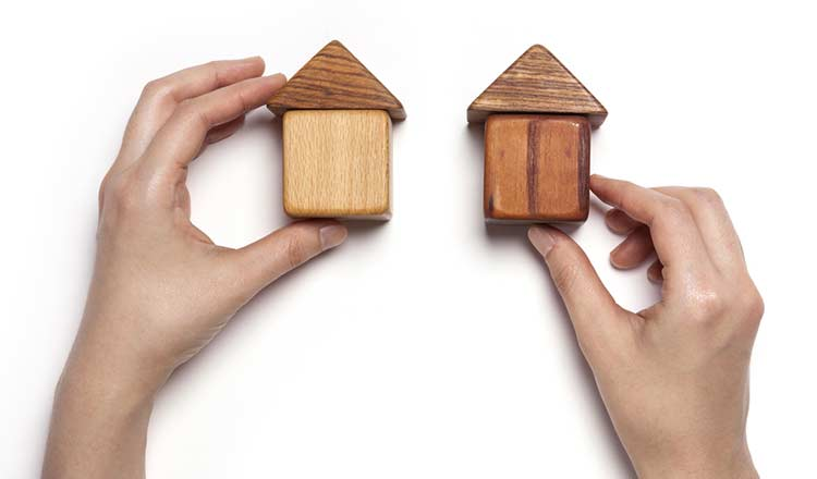 two hands holding wooden houses