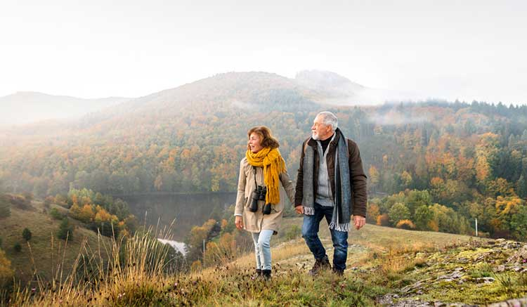 mature couple holding hands and walking in a scenic area