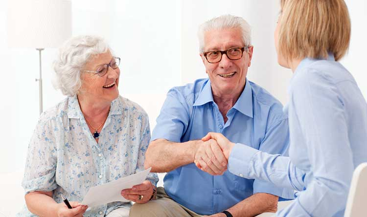 mature couple shaking hands with an adviser
