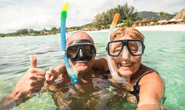 mature couple on holiday wearing snorkels in the sea and taking a selfie
