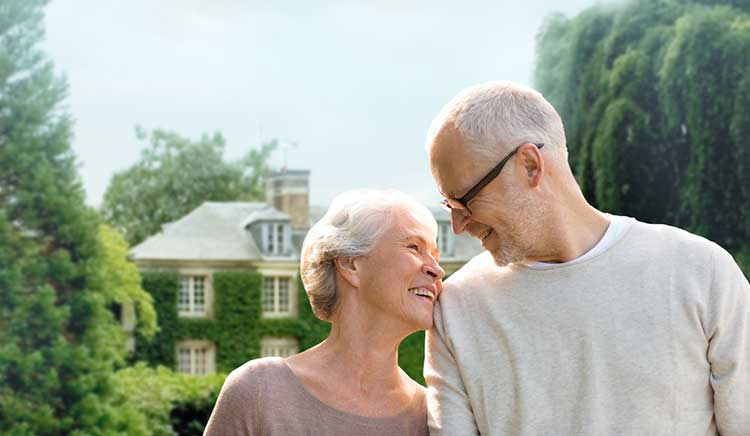mature couple smiling at each other in front of a house