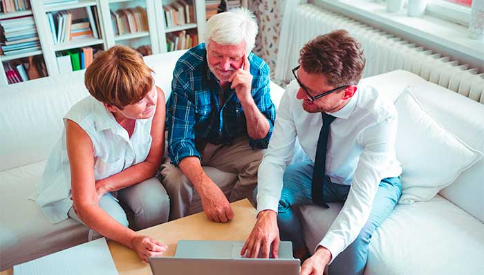 Equity release advice: Mature couple looking at a laptop with an adviser