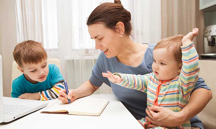 mum writing in a notebook with her children