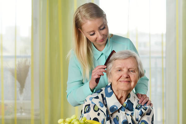 a daughter combs her elderly mothers hair