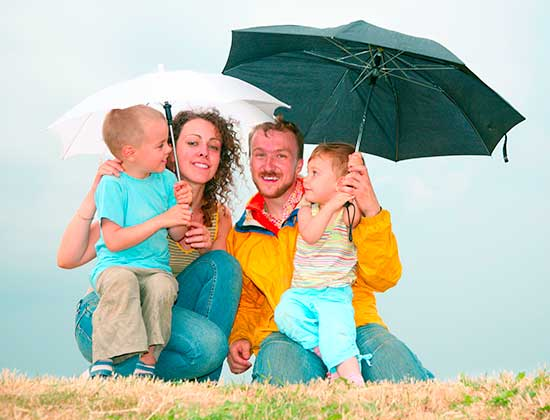 A family of four sitting under umbrellas on a hill