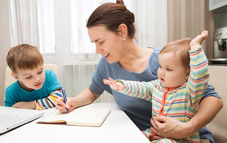 Life insurance for mums - mother with baby helps son with homework