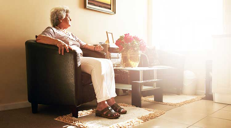 older lady sitting in a chair and looking out of a sunlit window