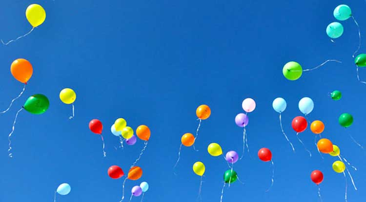 stunning blue sky filled with bright balloons floating away