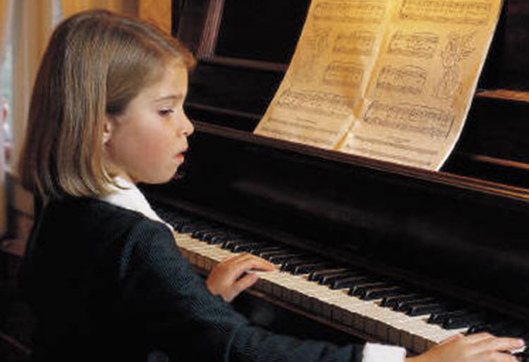 smartly dressed girl playing the piano