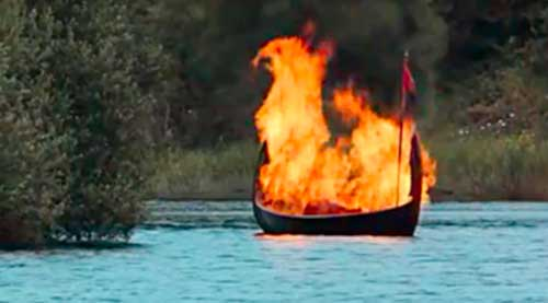 viking long boat on fire floating out to sea