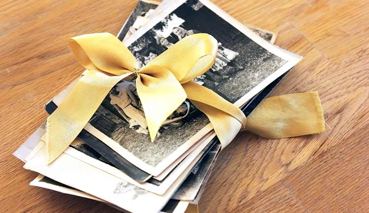 a pile of black and white photos tied with a yellow ribbon