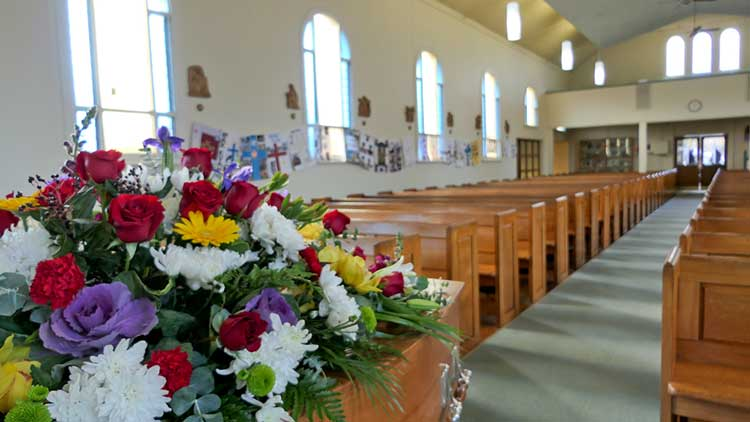 flowers on a coffin in an empty church