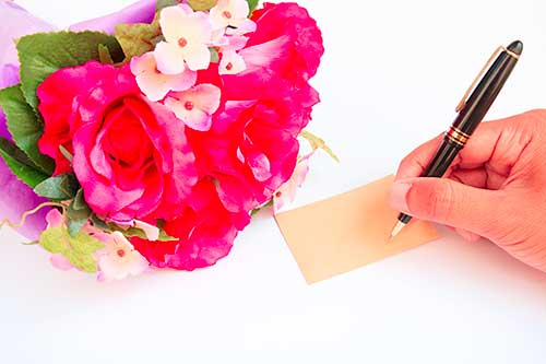 close up of hand writing a funeral flower card with a fountain pen