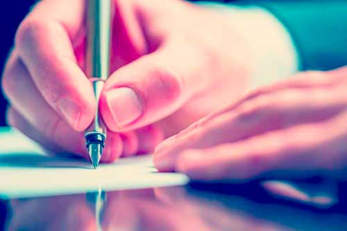 close up of mans hand writing a card with a fountain pen