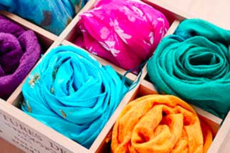 A wooden box of colourful scarfs