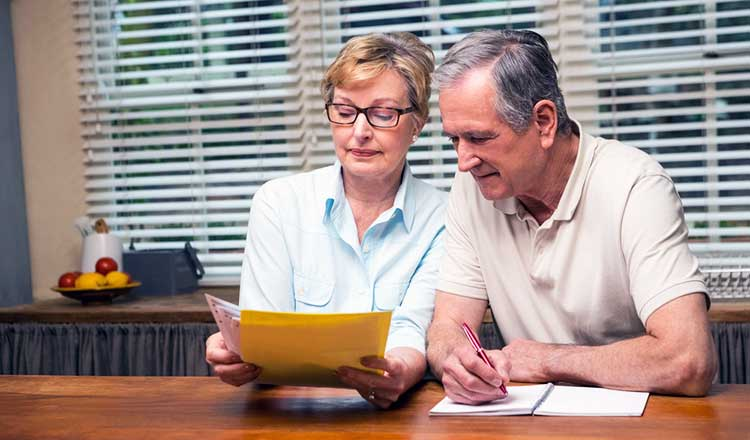 over 60s couple reviewing their finances