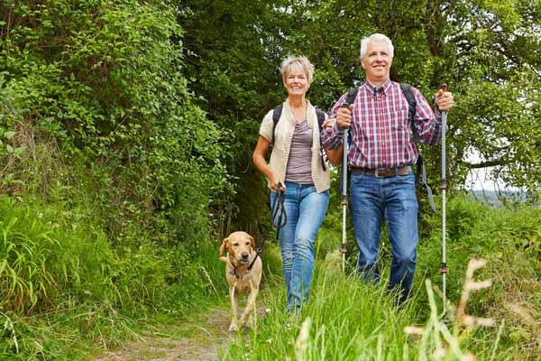 An older couple walk their dog in the countryside.