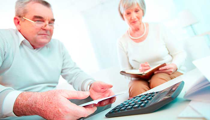 older couple sitting on sofa with a calculator and notepad