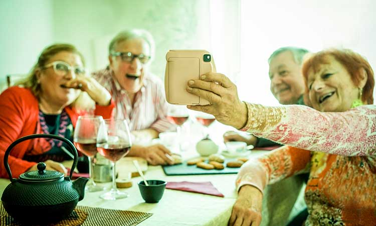 Over 50 plan for peace of mind: mature group of friends taking selfie