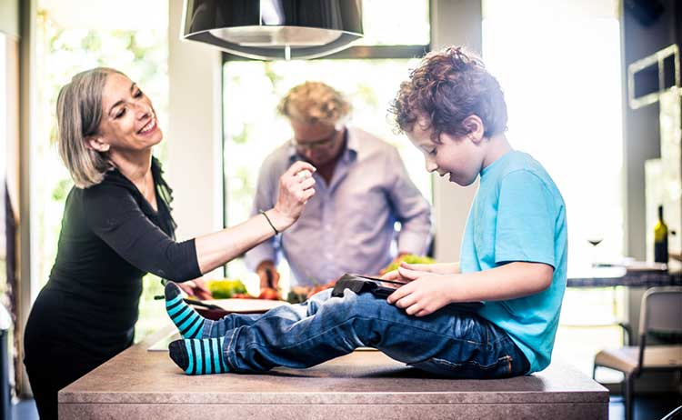Home insurance: Boy sitting on kitchen worktop with grandparents