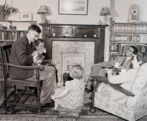 Family sat around a fireplace and young girl seated on a cushion on the floor in the middle of them