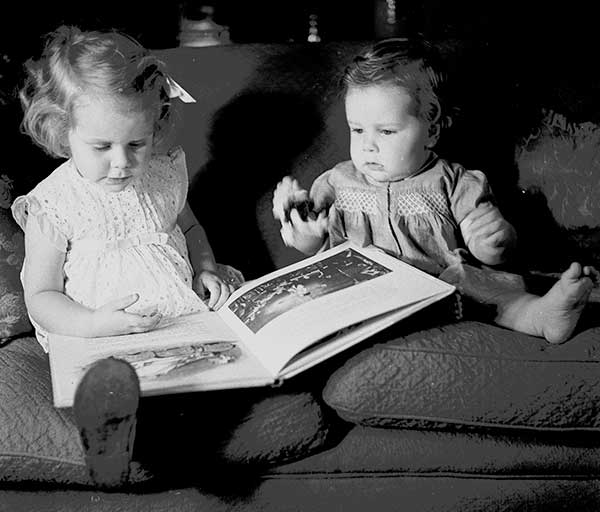 Two small children sat on a sofa and looking at a picture book